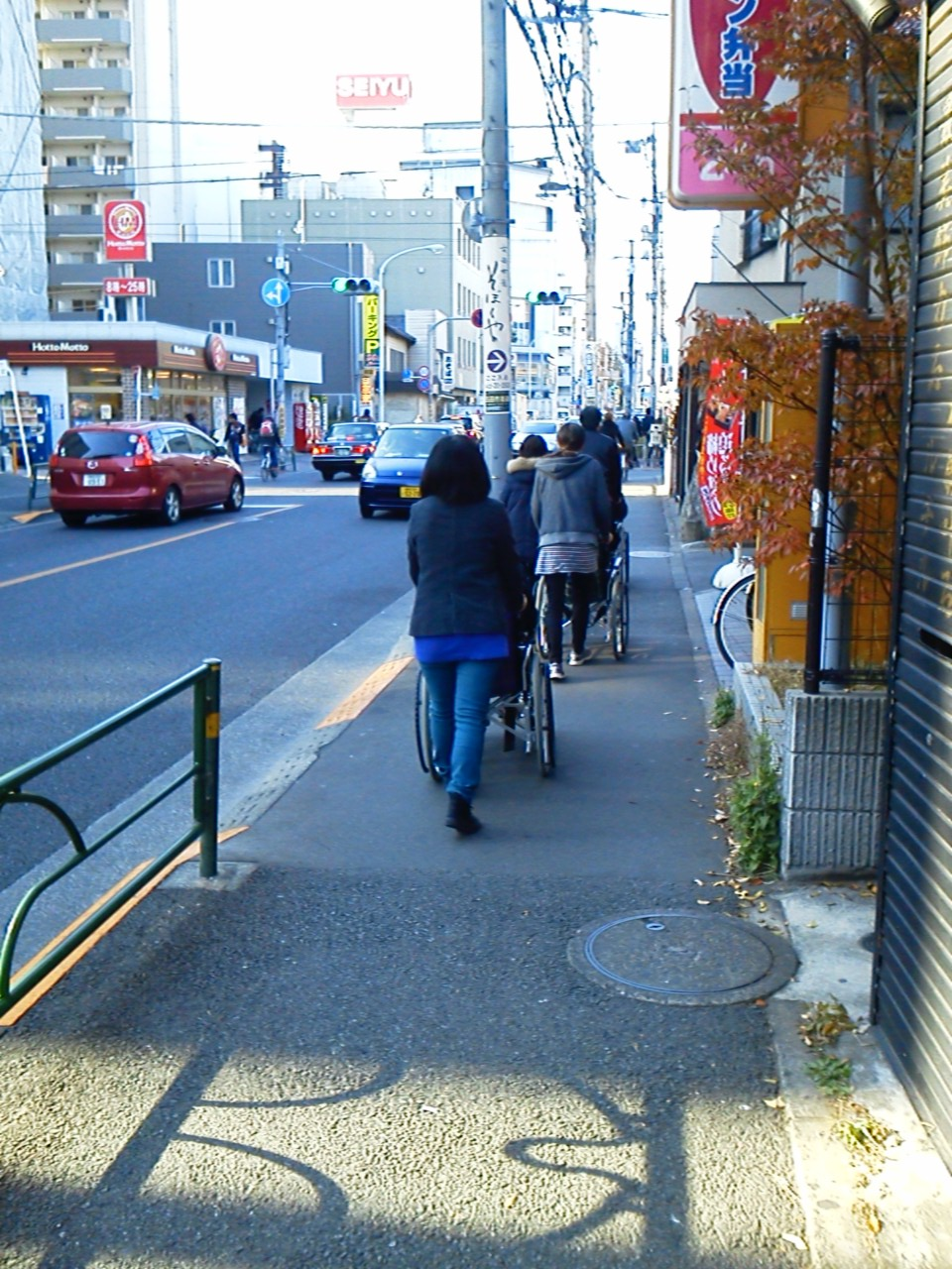 交通量の多い幹線道路脇の狭い歩道を進む